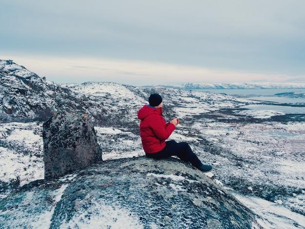 Eine tasse heißen tee in der hand eines mannes auf einem polarhügel