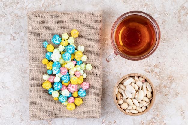 Eine tasse heißen tee mit bunten bonbons