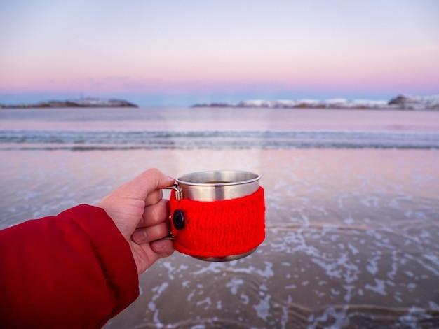 Eine tasse heißen tee mit dampf in der hand am arktischen ufer