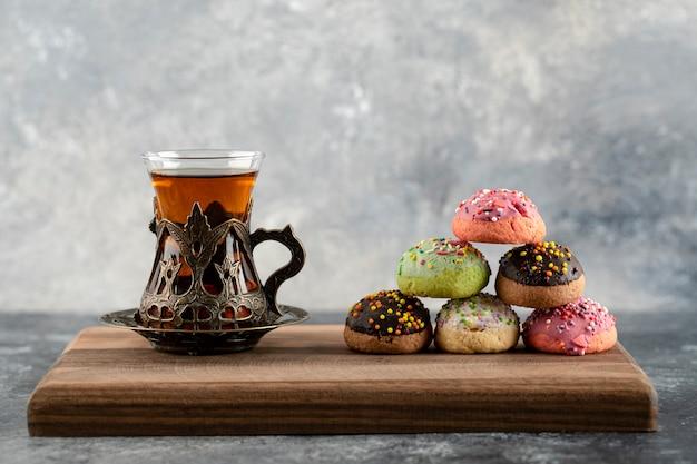 Eine tasse heißen tee mit donuts und streuseln.