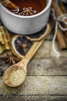 Eine tasse heißen tee mit einer zimtstange und einem löffel braunem zucker auf holz