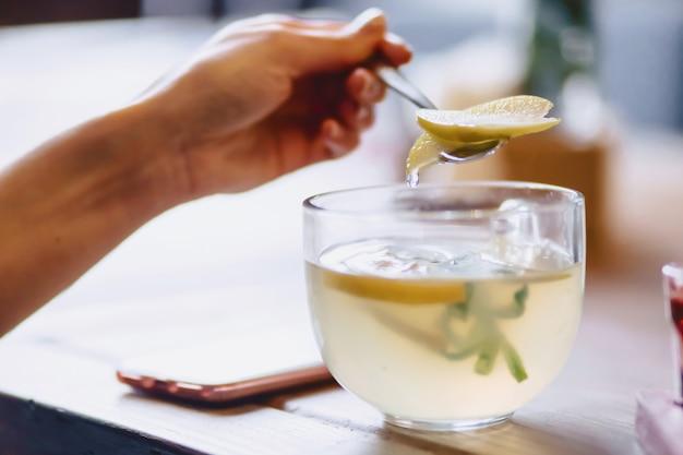 Eine tasse heißen tee mit minze und zitrone mischt das mädchen mit einem löffel