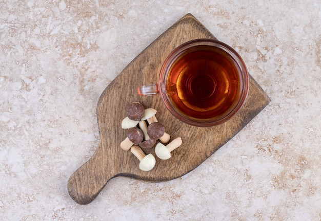 Eine tasse heißen tee mit süßen pilzen auf einem holzbrett