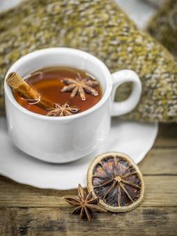 Eine tasse heißen tee mit zimtstangen, gewürzen und köstlicher getrockneter zitrone auf holz mit einem warmen pullover
