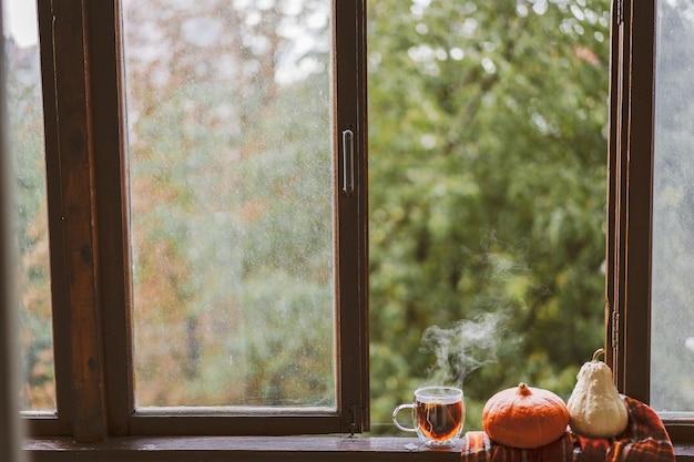 Eine tasse heißen tee und ein offenes buch auf einer vintage-fensterbank. lesen und ausruhen