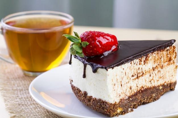 Eine tasse heißen tee und eine scheibe süßen kuchens mit schlagsahne, frischen erdbeeren und tropfender schokoladenglasur in einer weißen platte. süßer nachtisch
