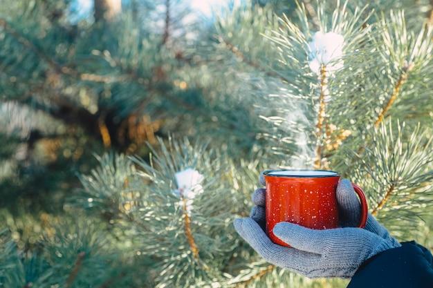 Eine tasse heißes getränk (tee, kaffee oder glühwein) in der winternatur. weibliche hand mit einer roten tasse. winter entspannen komfort und stimmung.