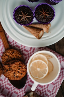 Eine tasse ingwer-zitronen-tee mit keksen und brownies.