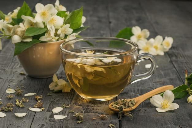 Eine tasse jasmintee und jasminblüten auf einem holztisch. ein belebendes getränk, das ihrer gesundheit gut tut.