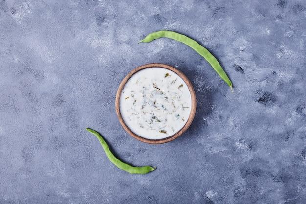 Eine tasse joghurtsuppe mit grünen bohnen.