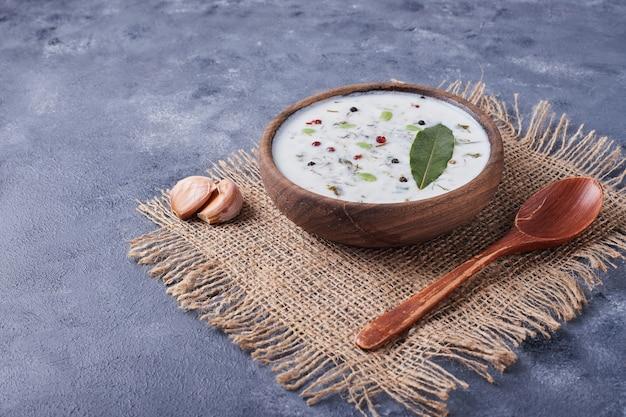 Eine tasse joghurtsuppe mit knoblauch.