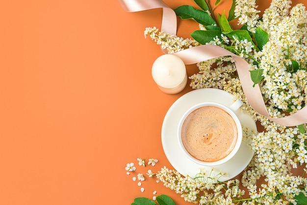 Eine tasse kaffee am morgen auf festlichem hintergrund mit blumen, kerzen und einem band auf terrakotta-hintergrund. ansicht von oben, horizontal.