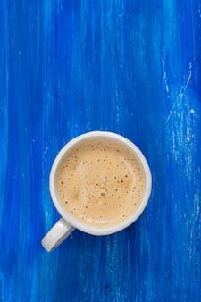 Eine tasse kaffee auf alter blauer holzoberfläche