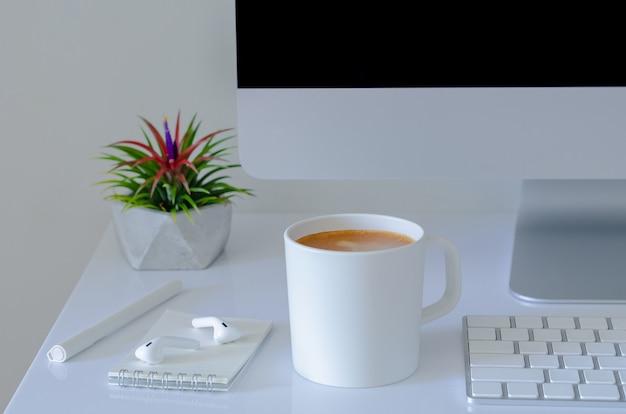 Eine tasse kaffee auf bürotisch mit luftpflanze tillandsia und modernem büromaterial.