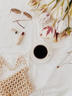 Eine tasse kaffee auf dem bett liegend mit weißen laken, tulpen, rotem lippenstift, gläsern, wenig püree und halskette