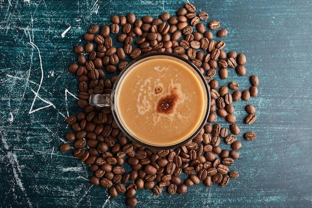 Eine tasse kaffee auf den bohnen, draufsicht.