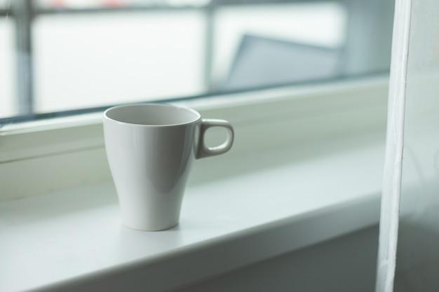 Eine tasse kaffee auf der fensterbank. großes fenster. skandinavischer stil. kopieren sie platz