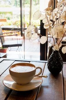 Eine tasse kaffee auf einem holztisch in einem café?