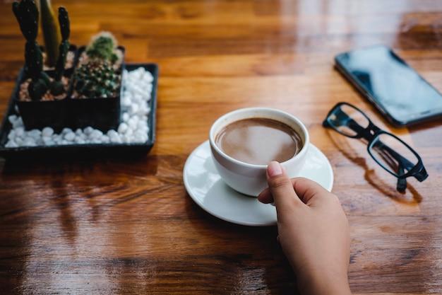 Eine tasse kaffee auf einem holztisch in einem café