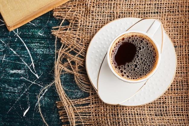 Eine tasse kaffee auf einem stück sackleinen.