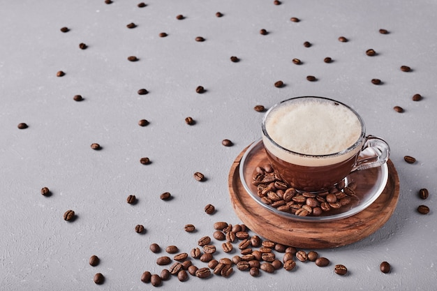 Eine tasse kaffee auf einer holzplatte.