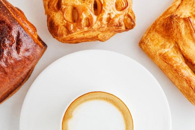 Eine tasse kaffee auf einer platte und brötchen herum auf einer weißen oberfläche