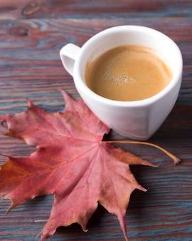 Eine tasse kaffee auf holztisch mit abgefallenen blättern. herbstzeit