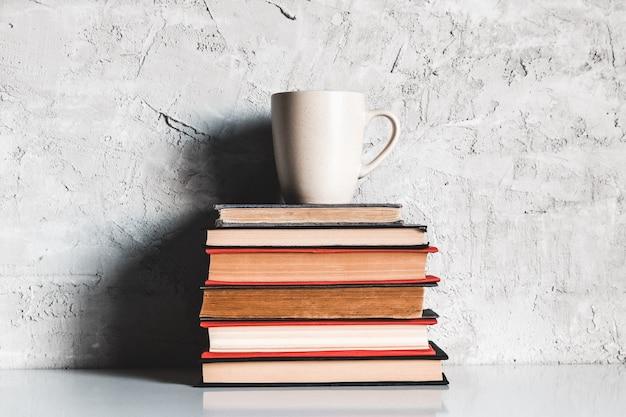 Eine tasse kaffee auf stapel bücher auf grauem hintergrund. bildung, studium, hobbys, lesen