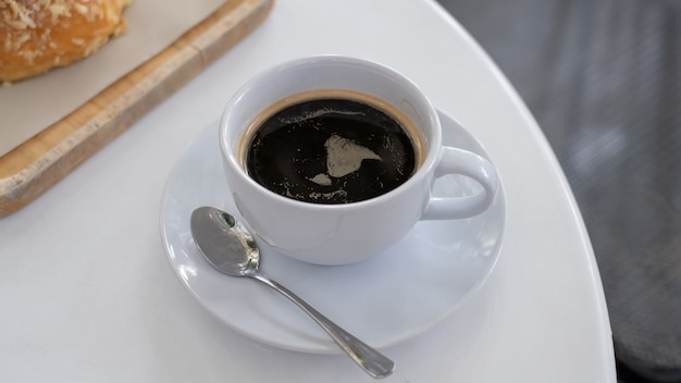Eine tasse kaffee auf weißem tisch mit arbeitspausenzeit, lebensmittelkonzept. schließen sie oben von einem glas heißer espressomischung erfrischungsgetränk mit kopierraum