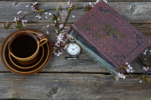 Eine tasse kaffee, bücher, eine taschenuhr und ein zweig blühender kirschen