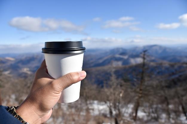 Eine tasse kaffee draußen im schnee trinken