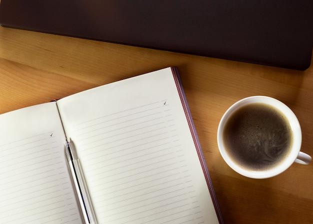 Eine tasse kaffee, ein notizbuch und ein laptop auf einem holztisch.