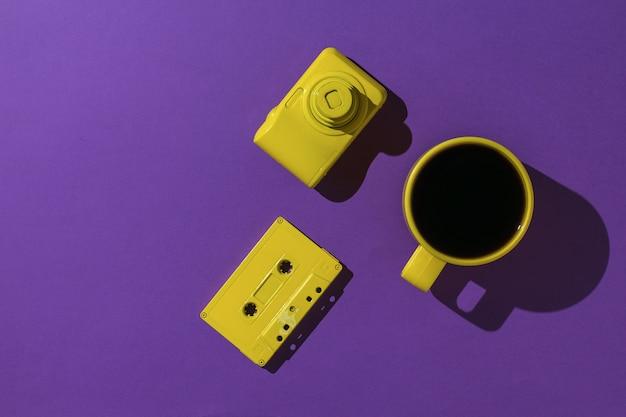 Eine tasse kaffee, eine gelbe kamera und eine kassette mit magnetband auf violettem hintergrund. farben-trend. flach liegen.