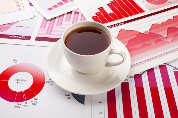 Eine tasse kaffee in den business-charts. desktop eines geschäftsmannes.