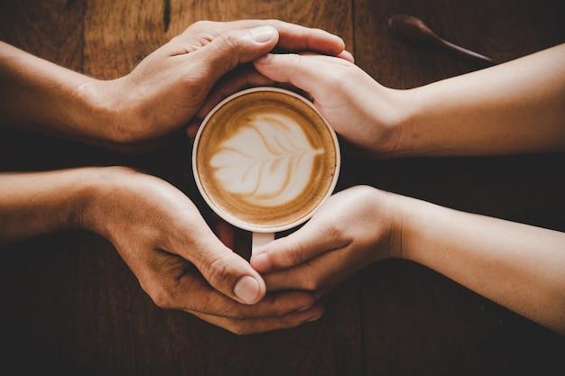 Eine tasse kaffee in den händen eines mannes und einer frau. tiefenschärfe.