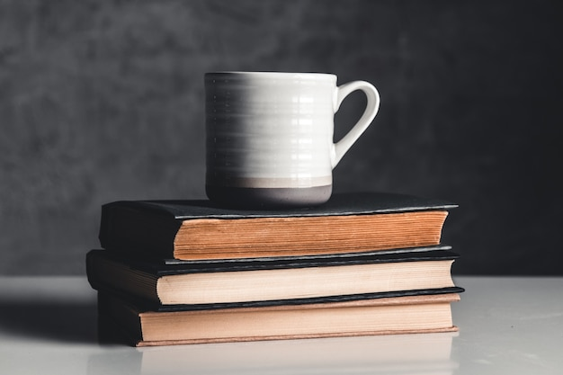 Eine tasse kaffee in der nähe eines stapel bücher auf grau