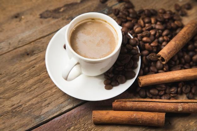 Eine tasse kaffee, kaffeesamen, zimt und ein buch auf einem holztisch