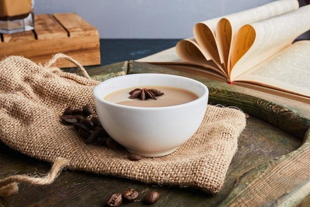 Eine tasse kaffee mit bohnen auf sackleinen.