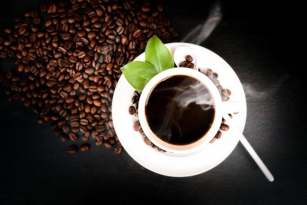 Eine tasse kaffee mit bohnen und blättern auf dem schwarzen holz.