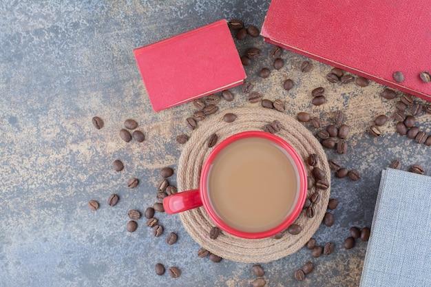Eine tasse kaffee mit buch und kaffeebohnen auf marmorhintergrund. foto in hoher qualität