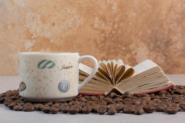 Eine tasse kaffee mit buch und kaffeebohnen auf weißem hintergrund. foto in hoher qualität