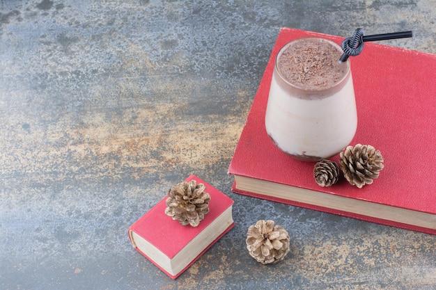 Eine tasse kaffee mit buch und tannenzapfen auf marmorhintergrund. foto in hoher qualität