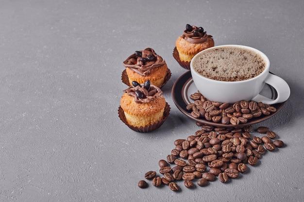 Eine tasse kaffee mit cupcakes.