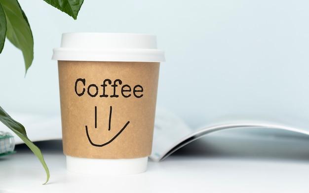 Eine tasse kaffee mit der aufschrift kaffee und einem emoticon auf dem desktop. konzept der kaffeepause.