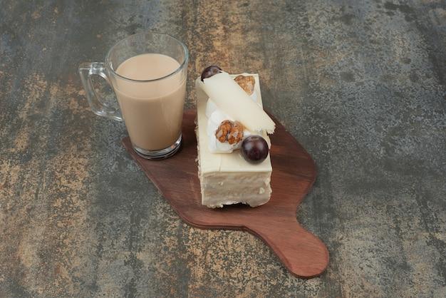 Eine tasse kaffee mit einem stück kuchen auf holzbrett.