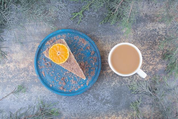 Eine tasse kaffee mit einem stück leckeren kuchens auf blauem teller. hochwertiges foto