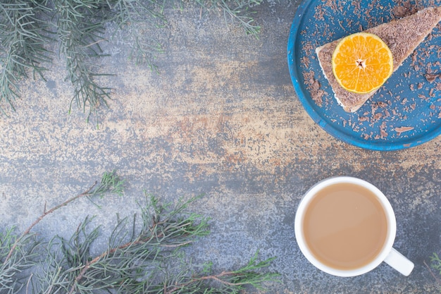 Eine tasse kaffee mit einem stück leckeren kuchens auf blauem teller.