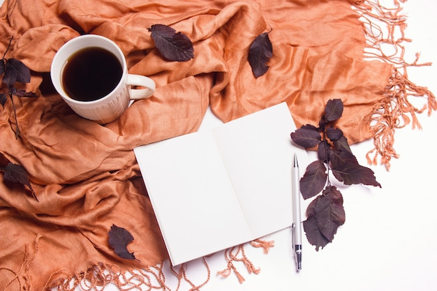 Eine tasse kaffee mit einem warmen schal, notizblock und blättern