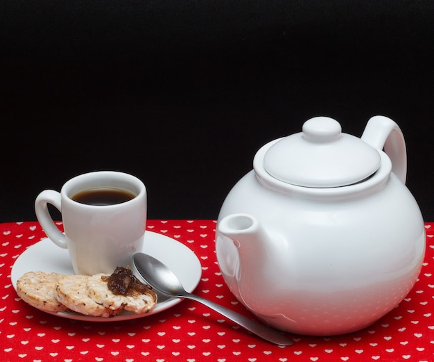 Eine tasse kaffee mit einer kaffeekanne unter dem roten stoff