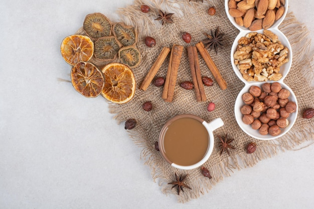 Eine tasse kaffee mit getrockneten orangen und nüssen auf marmorhintergrund. foto in hoher qualität